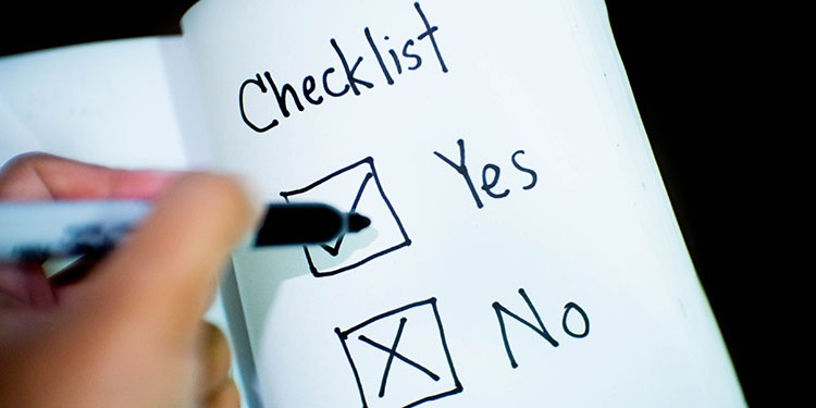 A hand with a pen checking Yes on a Yes/No checklist