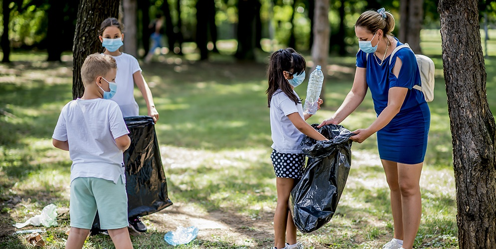 Woman with children collecting trash